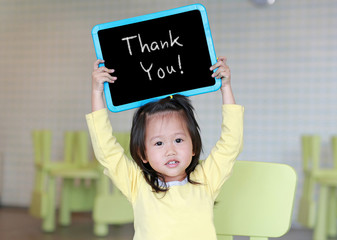 "Cute little child girl holding blackboard showing text "" Thank You "" in kids room. Education concept."