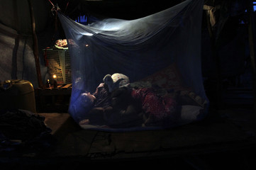 A Cambodian mother sleeps with her children in their shelter in the Blue Tent Community in Srah Po village northwest of Phnom Penh