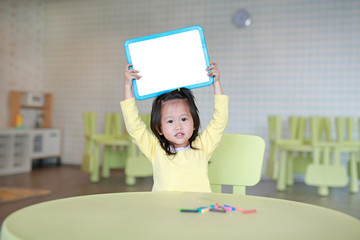 Cute asian child girl holding empty white blackboard in playroom.