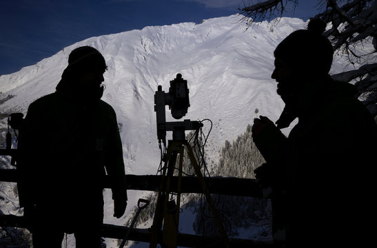 Scientists set up laser measurement equipment before triggering an avalanche at the Vallee de la Sionne in Anzere