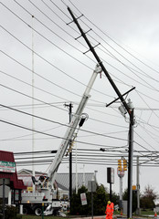 A utility pole is held in place by a truck crane after it snapped from the high winds of Hurricane Sandy in Pleasantville