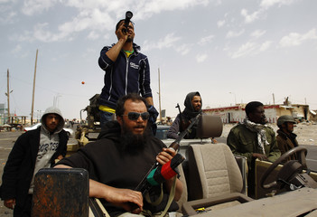 Rebel fighters look out from their vehicle on the road between Ajdabiyah and Brega, in Libya