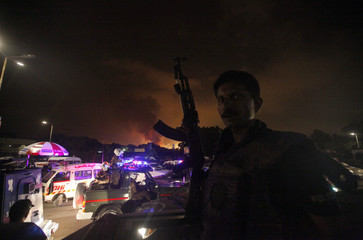 Policeman with a gun stands guard on a vehicle as smoke billows from Jinnah International Airport in Karachi