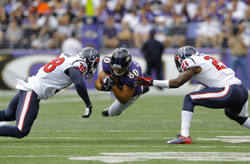 Ravens' Stokley dives for a first down after catching a pass against Texans' Manning and McCain during their NFL football game in Baltimore