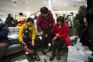 Women try on shoes in Macy's to kick off Black Friday sales in New York
