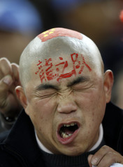 A China fan with the Chinese national flag painted on his head reacts before their 2011 Asian Cup Group A soccer match against Qatar in Doha