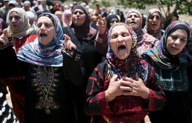 Relatives of Palestinian Abdullah Ghanayem mourn during his funeral in the village of Qafr Malik near the West Bank city of Ramallah