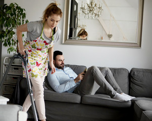 Woman doing chores using vacuum cleaner on carpet and lazy man on sofa