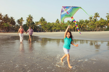 Happy mixed race asian family with child playing active outdoor games and having fun on the beach at sunset. Parents holiday and togetherness.