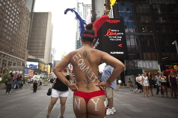 A woman who poses for tips wearing body paint and underwear poses for photos in Times Square in New York