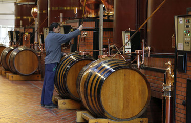 A technical expert works during a double distillation process in the distillery of Courvoisier cognac house in Cognac
