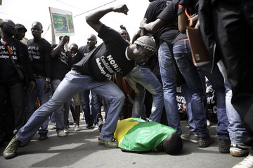 Senegalese anti-government protesters re-enact the death of a fellow protester at an opposition coalition rally during election campaigning in the capital Dakar