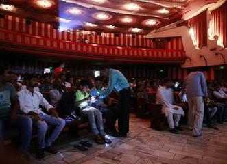 "Employee checks the tickets of cinema goers as they watch Bollywood movie ""Dilwale Dulhania Le Jayenge"" inside Maratha Mandir theatre in Mumbai"