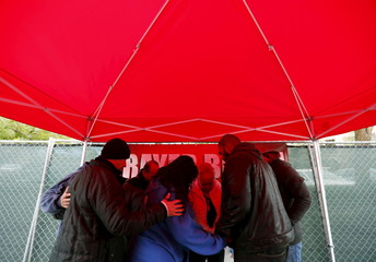 A prayer group prays outside the Inland Regional Center as employees return to work for the first time following a shooting in San Bernardino, California