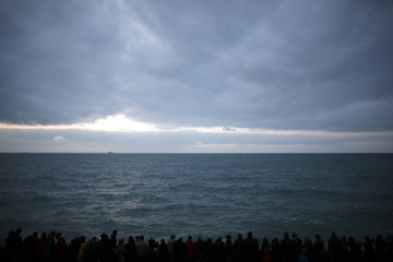 A crowd of people is seen in silhouette on the waterfront as people watch the incoming high tide in Saint Malo