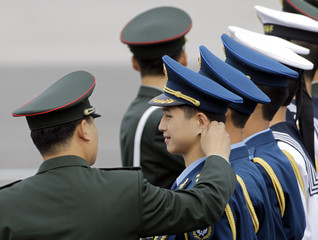 A military officer jokes with a member of the Chinese People's Liberation Army (PLA) honour guard in Beijing
