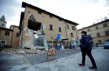 A police officer stands next to a collapsed building after an earthquake in Visso