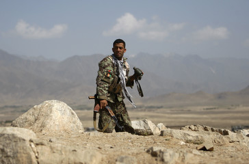 An Afghan National Army soldier takes his position at the site of an attack on the outskirts of Kabul