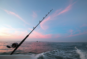 Fishing road on charter fishing boat against pink sunrise sky on the Sea of Cortes in Baja Mexico BCS
