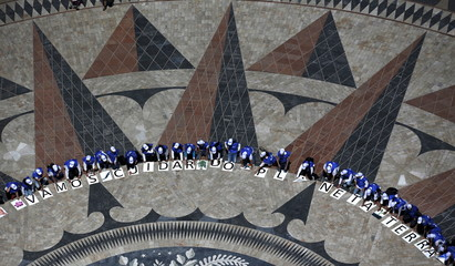 A group of volunteers gather on a square decorated with a giant world map, during Earth Day celebrations in Lisbon