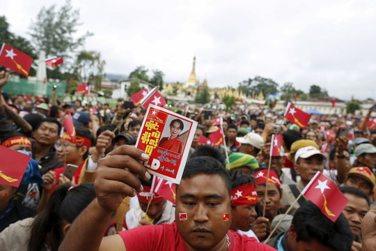 Man holds a sign as Myanmar pro-democracy leader Aung San Suu Kyi gives a speech on voter education at the Hopong township in Shan state
