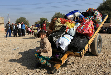 Displaced Iraqis flee from their homes at Shahrezad village east of Mosul