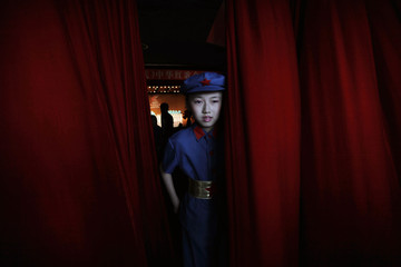 A schoolgirl participant walks through a red curtain during a revolutionary song singing competition to celebrate the upcoming 90th anniversary of the founding of the Communist Party of China, in Chongqing