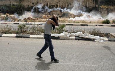 Palestinian protester covers his head and face from tear gas fired by Israeli troops during clashes at a protest in solidarity with prisoners on hunger strike, outside Ofer prison near the West Bank city of Ramallah