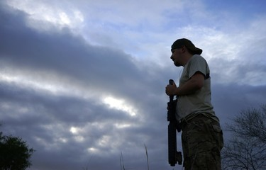 Will, holding his AR-15 rifle, looks across the Rio Grande river on the U.S. - Mexico border as he patrols at sunset outside Brownsville