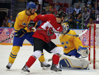 Canada's Toews scores on Sweden's goalie Lundqvist as Sweden's Berglund defends during first period of their men's ice hockey gold medal match  at Sochi 2014 Winter Olympic Games