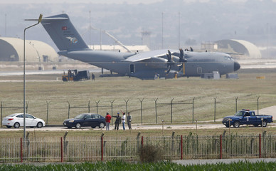 Turkish and U.S. soldiers, with a Turkish Air Force A400M tactical transport aircraft in the background, conduct inspections inside Incirlik airbase in the southern city of Adana, Turkey