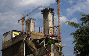 A woman enters her house, with cranes and construction work for the Rio 2016 Olympic Park seen in the background, at the Vila Autodromo favela in Rio de Janeiro