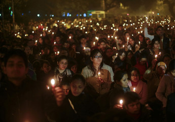 Demonstrators hold candles during a candlelight vigil for a gang rape victim who was assaulted in New Delhi