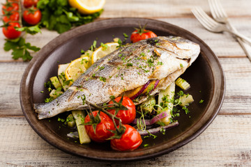 Baked whole fish, served with roasted vegetables and lemon.