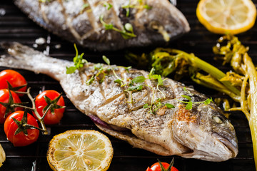 Grilled whole fish, served with roasted vegetables and lemon.
