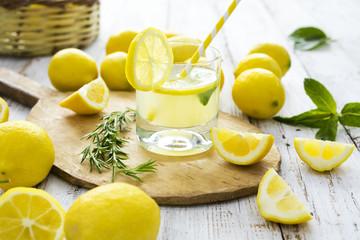 Lemon with lemonade on wooden background