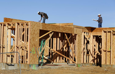 Workers build a single-family home as construction in a new subdivision is underway in San Marcos, California