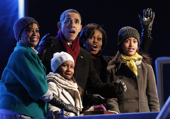 U.S. President Obama and his family react as his daughter Sasha pushes button to light National Christmas Tree, during a ceremony on the Ellipse in Washington