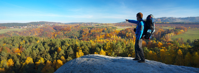 Tourist on the view point showing to an autumnal landscape