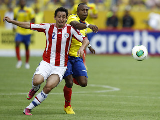 Piris of Paraguay challenges Benitez of Ecuador during their 2014 World Cup qualifying match in Quito