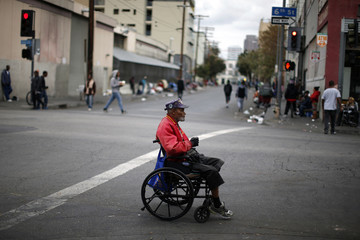 Homeless U.S. marine corps Korean War veteran Arthur Turner, 79, crosses the road on skid row in Los Angeles after a Veterans Day observance for homeless veterans at The Midnight Mission shelter