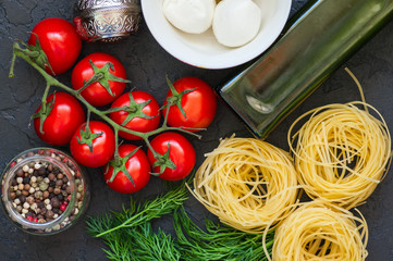 Ingredients for italian dinner. Olive oil, dill, cherry tomatoes, spices, mozzarella and italian whole grain pasta on a black slate background. Top view and copy space.