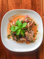 Sliced grilled pork salad Thai food on wood background