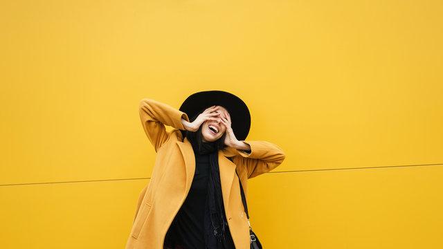 Stylish cheerful woman at yellow wall