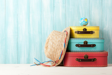 Travel concept with retro style suitcases, straw hat and globe on blue wooden background