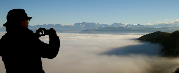 Fog covers the landscape in front of the eastern Swiss Alps as a man takes pictures from a lookout near Albis Pass mountain pass