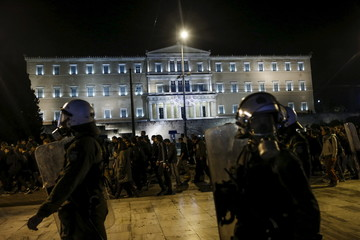 Protesters, escorted by riot police, march past the parliament building in Athens