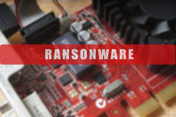 Blurred of a circuit board with big microchip . Cyber security concept with ransonware text