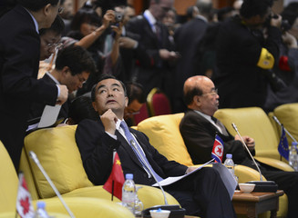 China's Foreign Minister Wang talks to his staff as he sits next to his North Korean counterpart Pak while they wait for retreat session during the 20th ASEAN Regional Forum in Bandar Seri Begawan