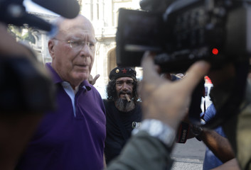 Democratic Senator Patrick Leahy of Vermont speaks to reporters as a street entertainer impersonating Cuban Revolution leader Che Guevara stands beside him in Havana
